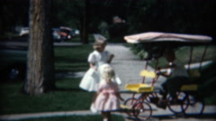 1957: Kids playing on the sidewalk with old tyme cover peddle cart. Stock Footage
