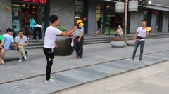 Young people playing tennis balls on the street Qianmen street, Beijing Stock Footage
