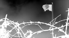 Flag and rusty barbed wire. Battlefield, war site - Negative, black and white. - stock footage