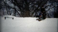 1957: Family sledding in a toboggan on a gentle slope in deep snow. Stock Footage