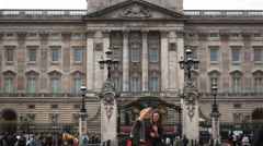 Two young female tourists pose for a photo at buckingham palace, london Stock Footage