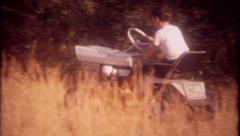 2845 - cutting the grass with the riding lawn mower - vintage film home movie Stock Footage