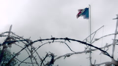 French flag and rusty barbed wire. Old battlefield, war site - slow motion Stock Footage