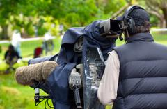 Camera operator shooting on location event - stock photo