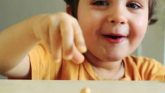 A cheerful boy is having fun. He is smiling, giggling and playing with a nut. Stock Footage