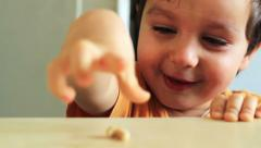 A cheerful boy is having fun. He is smiling, giggling and playing with a nut Stock Footage