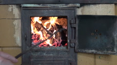 Handpoking fire burning in  fireplace with rake Stock Footage
