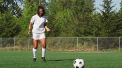 Female soccer player receives a soccer ball and kicks it down the field - stock footage