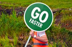 Unrecognizable road worker holds Go Faster traffic road signpost Stock Photos