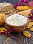 Flour amaranth in clay bowl with cookies on board Stock Photos