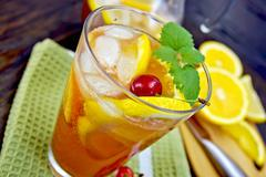 Lemonade with cherry in glassful on board - stock photo