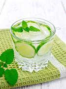 Lemonade with cucumber and mint in glassful on napkin - stock photo