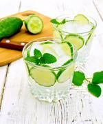 Lemonade with cucumber and mint in two glassful on light board - stock photo
