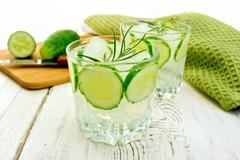 Lemonade with cucumber and rosemary in two glassful on board - stock photo