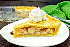 Pie apple with whipped cream in plate on board - stock photo