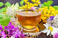Tea from flowers in glass cup on board - stock photo