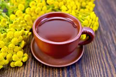 Tea from tansy in clay cup on board - stock photo