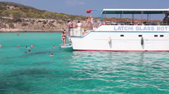 People swim in the Blue Lagoon while ships are waiting. Latchi, Cyprus Stock Footage