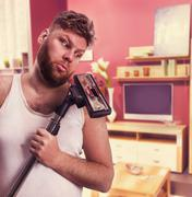 Adult man looks at the vacuum cleaner Stock Photos