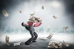 Businessman loaded with huge amount of money Stock Photos