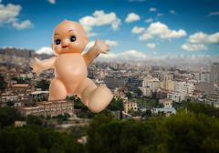 Giant baby doll goes across the town - stock photo
