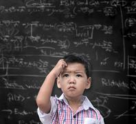 Thinking child with a blackboard in the background Stock Photos