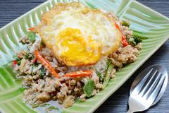 Rice topped with stir-fried pork ,basil and Fried Egg - stock photo