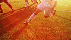 Close up of a soccer player slide tackling at sunset - stock footage