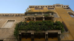 Yellow building with balconies covered with green plants in Venice Stock Footage