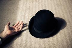 Dead man and hat on floor - stock photo