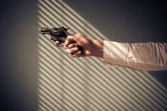 Man pointing revolver by window - stock photo