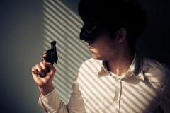 Man with gun by window - stock photo