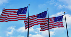 Three American Flags fluttering against light blue sky Stock Footage