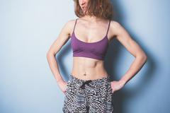 Young woman with toned abs in sports clothing - stock photo