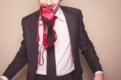 Businessman with bra in his mouth Stock Photos