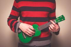 Man in striped jumper playing ukulele Kuvituskuvat