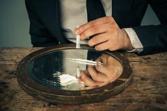 Businessman snorting cocaine Stock Photos