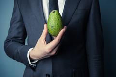 Businesman holding avocado - stock photo