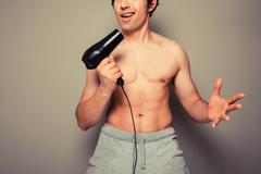 Athletic young man with a hair dryer - stock photo
