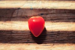 Unusual heartshaped tomato on wood table - stock photo