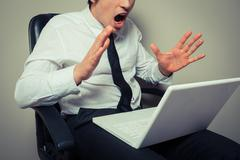 Nervous businessman wih laptop - stock photo