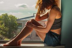Young woman sitting on window sill on sunny day - stock photo