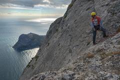 Man climber on edge of steep mountainside in Crimea. Stock Photos