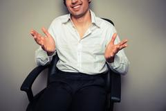 Casual young businessman in office chair Stock Photos