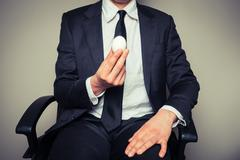 Businessman holding an egg Stock Photos
