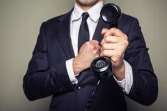 Businessman handing over a telephone Stock Photos