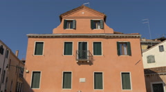 View of a red building with old window shutters in Venice - stock footage