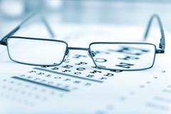 Clear Black modern glasses on a eye sight test chart - stock photo