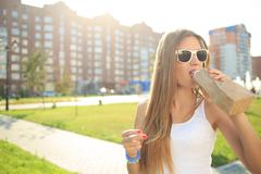 girl drinking from a paper bag in the street. smokes. decadence, anti-social - stock photo