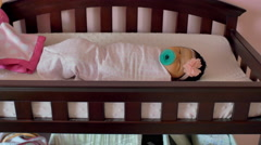 A newborn baby wrapped in a blanket, laying in a crib in a nursery - stock footage